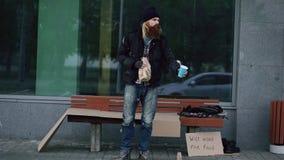 El hombre sin hogar muy borracho con la muestra de la cartulina y del alcohol pide dinero mientras que coloca el banco cercano en foto de archivo libre de regalías