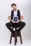 El hombre smilling hermoso joven con la barba en la camisa blanca y la tenencia negra del chaleco hacen tabletas y se sientan en  Imagen de archivo