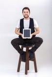 El hombre smilling hermoso joven con la barba en la camisa blanca y la tenencia negra del chaleco hacen tabletas y se sientan en  Imágenes de archivo libres de regalías