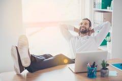 El hombre soñador joven hermoso se está sentando en el lugar de trabajo que pone hola imagen de archivo libre de regalías