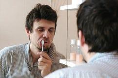El hombre soñoliento cansado con una resaca que acaba de despertar el cepillo sus dientes, mira su reflexión en el espejo fotos de archivo