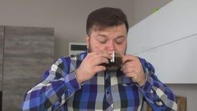 El hombre soñoliento con una barba sostiene una taza de café en sus manos y huele el aroma del café que vigoriza, primer, cámara  almacen de metraje de vídeo