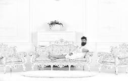 El hombre soñoliento en albornoz bebe el café en hotel de lujo por la mañana, fondo blanco Concepto de lujo de la vida Hombre con imágenes de archivo libres de regalías