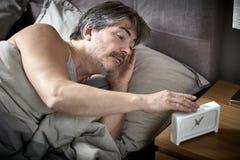 El hombre soñoliento en cama despierta imagen de archivo