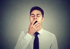 El hombre soñoliento que bosteza con entrega la boca foto de archivo