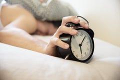 El hombre soñoliento que sostiene el despertador por la mañana con atrasado despierta imagenes de archivo