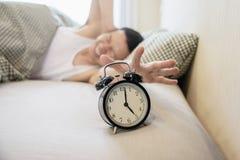 El hombre soñoliento que sostiene el despertador por la mañana con atrasado despierta fotografía de archivo