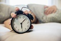 El hombre soñoliento que sostiene el despertador por la mañana con atrasado despierta fotografía de archivo libre de regalías
