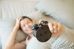 El hombre soñoliento que sostiene el despertador por la mañana con atrasado despierta foto de archivo libre de regalías