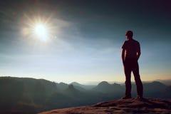 El hombre solo en casquillo rojo en pico del pico agudo en imperios de la roca parquea y vigilando el valle brumoso y de niebla d Foto de archivo libre de regalías