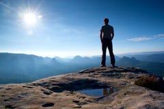 El hombre solo en casquillo rojo en pico del pico agudo en imperios de la roca parquea y vigilando el valle brumoso y de niebla d Fotografía de archivo