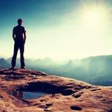 El hombre solo en casquillo rojo en pico del pico agudo en imperios de la roca parquea y vigilando el valle brumoso y de niebla d Fotos de archivo