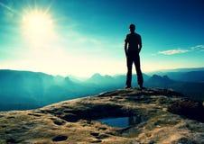 El hombre solo en casquillo rojo en pico del pico agudo en imperios de la roca parquea y vigilando el valle brumoso y de niebla d Imagen de archivo