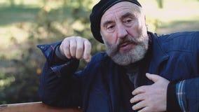 El hombre solo, envejecido siente dolor y restos de pecho en banco de la calle almacen de metraje de vídeo