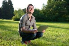El hombre sonríe con la computadora portátil imagen de archivo