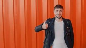 El hombre sonriente alegre con un bigote y demostraciones de la barba manosea con los dedos para arriba o gesto del gusto almacen de video