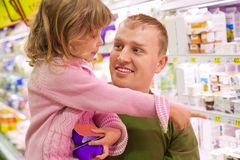 El hombre sonriente con la muchacha compra yogur en supermercado Imagenes de archivo