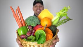 El hombre sonriente del granjero lleva a cabo cierre orgánico fresco de la cesta de las legumbres de frutas encima del retrato almacen de metraje de vídeo