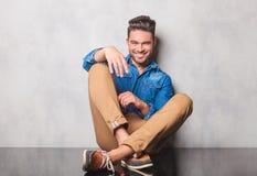 El hombre sonriente en piernas que se sentaban de la camisa del dril de algodón cruzó en backgr del estudio Foto de archivo