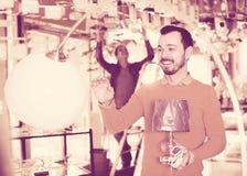 El hombre sonriente en una tienda más ligera está eligiendo la lámpara elegante y moderna Foto de archivo