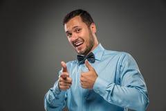 El hombre sonriente está gesticulando con la mano, señalando el finger en la cámara Imágenes de archivo libres de regalías