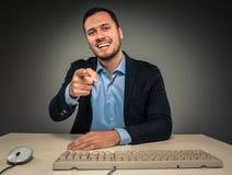 El hombre sonriente está gesticulando con la mano, señalando el finger en la cámara Imagen de archivo libre de regalías