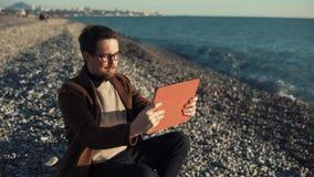 El hombre sonriente está haciendo la llamada video por la tableta en un Pebble Beach, agitando la mano almacen de video