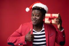 El hombre sonriente está sosteniendo la caja de regalo con la cinta roja fotografía de archivo libre de regalías