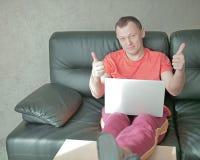 El hombre sonriente joven con el ordenador portátil se sienta en el sofá en casa y detiene los pulgares, las miradas en cámara imagenes de archivo