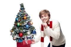 El hombre sonriente joven pone el regalo bajo el árbol de navidad Foto de archivo
