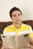 El hombre sonriente leyó el periódico Imagen de archivo libre de regalías