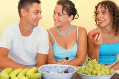 El hombre sonriente y las mujeres jovenes comen la fruta en sitio acogedor fotografía de archivo libre de regalías