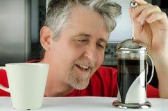 El hombre soñoliento feliz con el francés presiona el fabricante de café Fotos de archivo libres de regalías