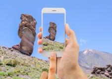 El hombre soporta el teléfono de la cámara en el Teide imagen de archivo