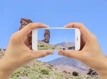 El hombre soporta el teléfono de la cámara en el Teide foto de archivo libre de regalías