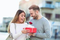 El hombre sorprende a la mujer con un regalo y subió foto de archivo