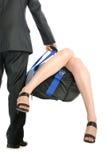 El hombre sostiene el bolso con pegar hacia fuera pies femeninos Foto de archivo