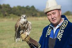 El hombre sostiene el halcón, circa Almaty, Kazajistán Imagenes de archivo