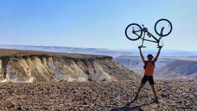 El hombre sostiene la bicicleta en un pico Fotos de archivo libres de regalías