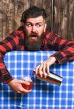 El hombre sostiene la coctelera en fondo del mantel de la tela escocesa Foto de archivo