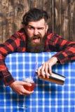 El hombre sostiene la coctelera en fondo del mantel de la tela escocesa Fotos de archivo