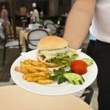 El hombre sostiene la placa con el cheeseburger con las patatas fritas, cortadas fotografía de archivo libre de regalías