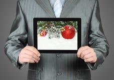 El hombre sostiene la tableta con la composición de la Navidad Imagen de archivo