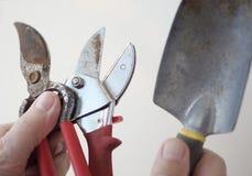 El hombre sostiene los utensilios de jardinería viejos Foto de archivo libre de regalías