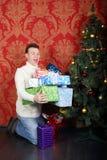 El hombre sostiene muchos regalos cerca del árbol de navidad Foto de archivo