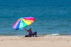 El hombre sostiene el parasol de playa en un día ventoso fotos de archivo libres de regalías