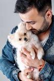 El hombre sostiene el perro pomeranian foto de archivo libre de regalías