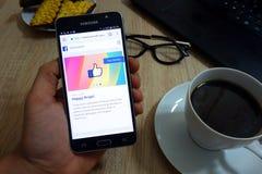 El hombre sostiene el smartphone de Samsung con página web de la redacción de Facebook en la pantalla foto de archivo libre de regalías