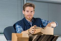 El hombre sostiene sobres en oficina Imagen de archivo
