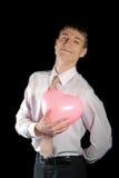 El hombre sostiene un globo rosado del corazón Imagen de archivo libre de regalías